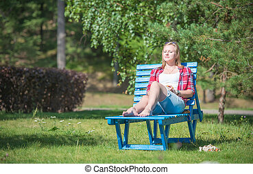 Young beautiful woman tanning on the sun lounger