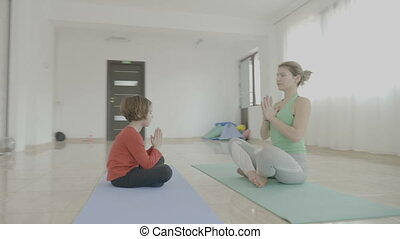 Young beautiful woman teaching yoga poses to a little child girl and how to meditate on a mat in a fitness studio