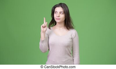 Young beautiful woman thinking while pointing finger up