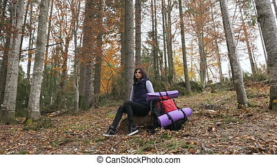 Young beautiful woman tourist sitting on halt in forest. Beautiful brunette tourist girl sits in the forest near her red backpack. , Autumn tourism concept