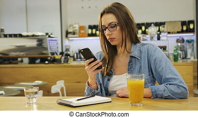 Young beautiful woman typing on smartphone and drinking juice in cafe