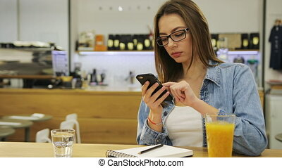 Young beautiful woman typing on smartphone, surfing the internet and drinking juice in cafe