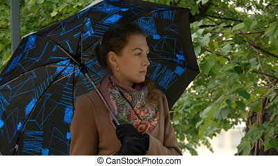 Young beautiful woman under an umbrella in a city park. It's raining, sad and disappointed