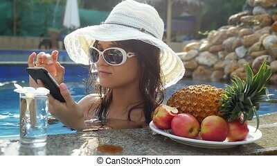 Young beautiful woman uses mobile phone in swimming pool drinks water next to the plate with tropical fruits.