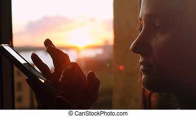 Young beautiful woman uses the phone, standing at the window on the background of a beautiful sunset with sun flare
