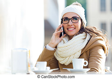 Young beautiful woman using her mobile phone in a cafe.