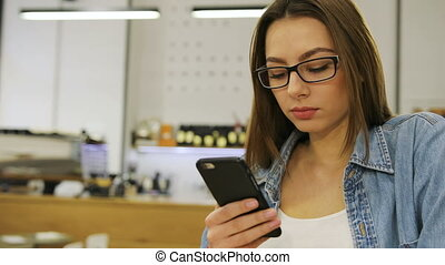Young beautiful woman using mobile phone, texting massege, sending sms while sitting in cafe