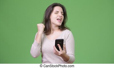 Young beautiful woman using phone and getting good news -...
