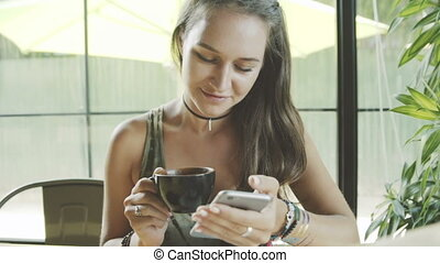 Young beautiful woman using smartphone in cafe