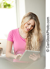 young beautiful woman using tablet at home