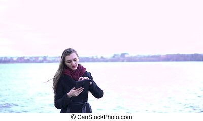 Young beautiful woman using tablet near lake