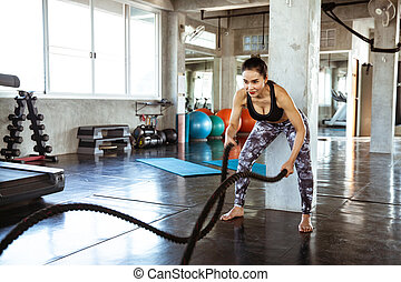 Young beautiful woman using training ropes in a gym