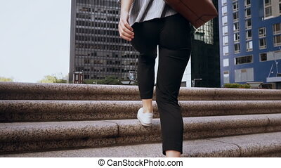 Young beautiful woman walk upstairs to the office in...