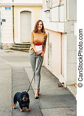 Young beautiful woman walking down the road with her dog on a leash, holding white box with red roses
