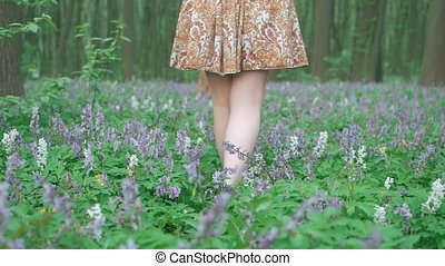 Young beautiful woman walking forest among the flowers