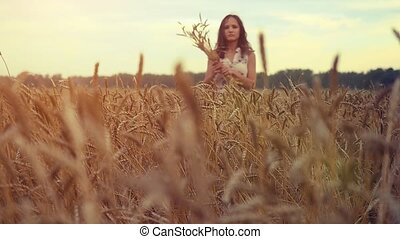Young beautiful woman walking in a wheat field. Hand of a young girl touching corn ears in a field at sunset in slowmotion. 1920x1080