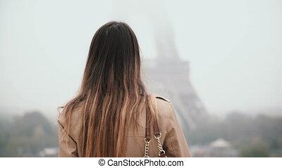 Young beautiful woman walking in downtown near the Eiffel...