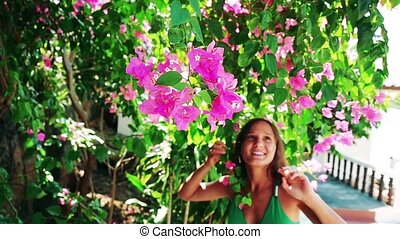 Young beautiful woman walking in the garden of pink flowers, touches and smells flowers and smiles. slow motion.