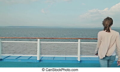 Young beautiful woman walking on deck of cruise ship and enjoying at view.