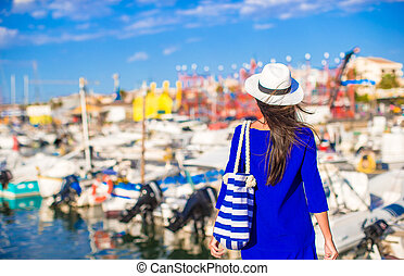 Young beautiful woman walking on dock near the boat