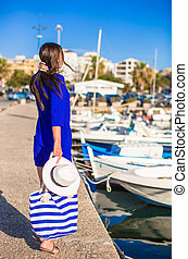 Young beautiful woman walking on dock near the boat