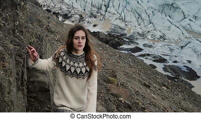 Young beautiful woman walking through the rocks, hiking in the mountains near the Vatnajokull glaciers lagoon in Iceland