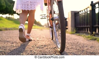 Young beautiful woman walking with a bicycle at sunset. Slow motion
