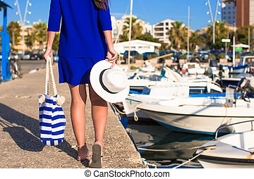Young beautiful woman walking with hat and bag on dock near the boat