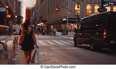 Young beautiful woman walking with shopping bags, crossing the traffic road in downtown of New York, America.