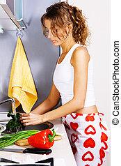 Young beautiful woman washing vegetables