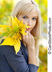 Young beautiful woman with a bouquet of autumn leaves