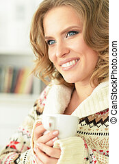 woman with a cup of tea on sofa