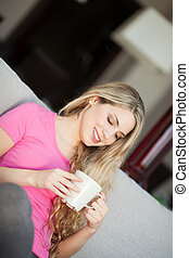 young beautiful woman with a cup on sofa