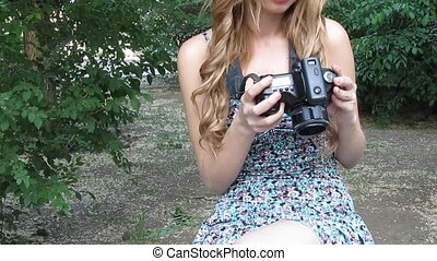 Young beautiful woman with a digital camera