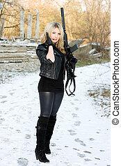 Young beautiful woman with a gun