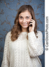 Young beautiful woman with a mobile phone against a background of vintage wallpaper