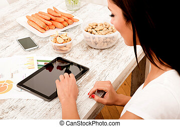 A young beautiful woman using a Tablet computer at home in the kitchen.