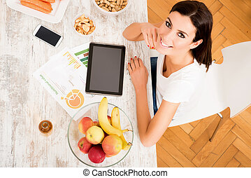 Young beautiful woman with a Tablet PC at home - A young...