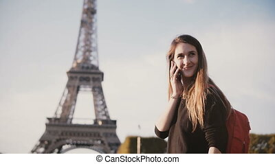 Young beautiful woman with backpack standing near the Eiffel...