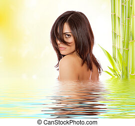 Young beautiful woman with bamboo and reflection