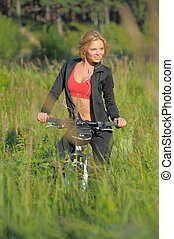 Young beautiful woman with bicycle listening to music in park