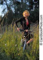Young beautiful woman with bicycle resting in park on sunset