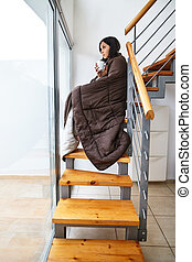 Young beautiful woman with blanket drinking hot coffee sitting on stairs