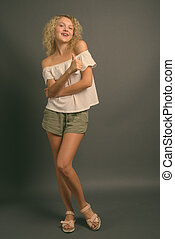 Young beautiful woman with blond curly hair against gray background