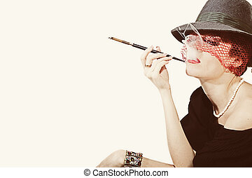 Young beautiful woman with cigarette in mouthpiece in hat with veil on light background