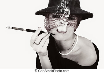 woman with cigarette in mouthpiece in hat with vei