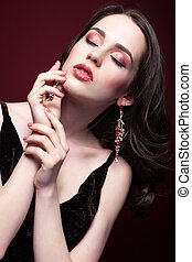 Young beautiful woman with closed eyes on red marsala...