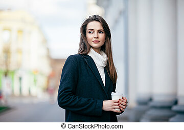Young beautiful woman with cup of coffee in city street