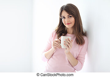 Young beautiful woman with cup of coffee on white background