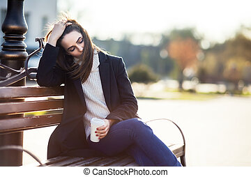 Young beautiful woman with cup of coffee sitting on bench in big city